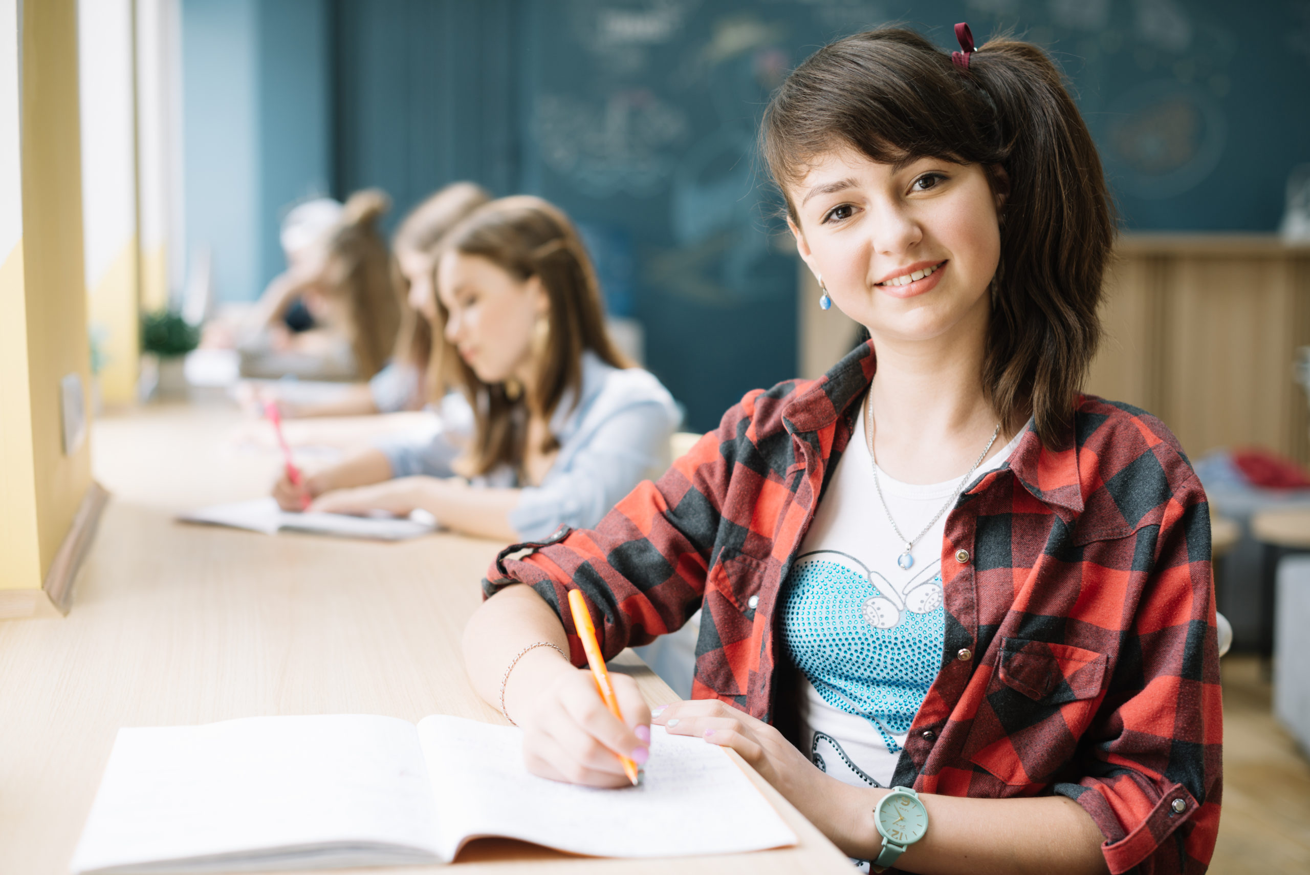 smiling-student-with-notepad-in-class